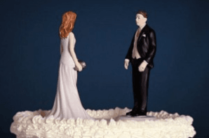 Top of a wedding cake: husband and wife standing facing each other