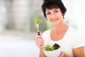 Woman holding bowl of lettuce