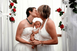 Two women in a same sex relationship kissing at their wedding holding a baby