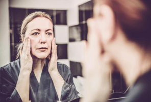 older woman looking at skin in mirror