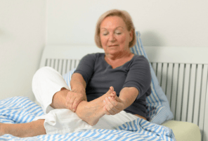 older lady looking at feet on bed
