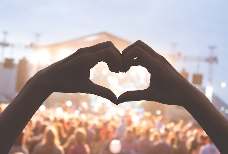 Concert crowd with hands showing a love heart