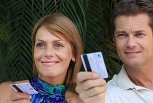 Man and woman both holding out credit cards