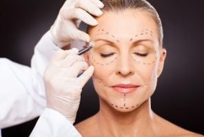 middle aged woman with correction marks preparing for plastic surgery
