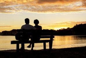 The Silhouette of a couple watching a beautiful sunset together while sitting on a bench