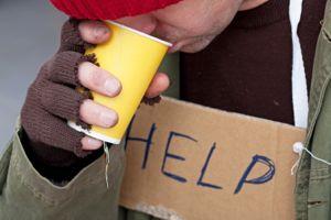 Homeless with cardboard on his neck drinkig hot tea