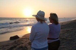 two women on a beach watching sunset