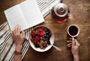 cropped view of woman reading book during breakfast