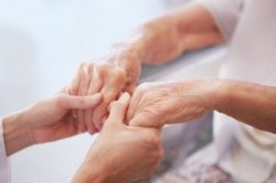 Younger woman holding the hands of an older woman