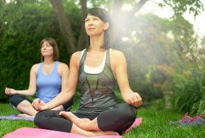 Couple of female friends in their forties connecting and staying healthy by practicing yoga i