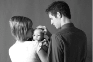 black and white photo of a couple holding a baby