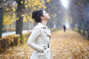 Woman breathing deeply against an autumn scene
