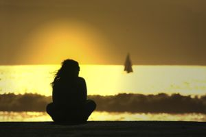Woman looking out to sea at sunset