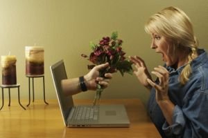 Man giving a woman a bunch of red roses through a computer screen