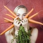 Woman holding a bunch of carrots