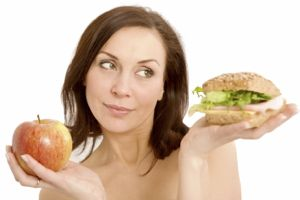 Woman balancing up whether to eat a burger or an apple