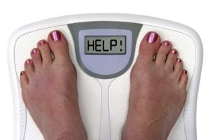 Woman's feet on scales with the word 'help' in the reader