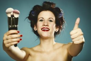 woman holding make up brushes and giving the thumbs up