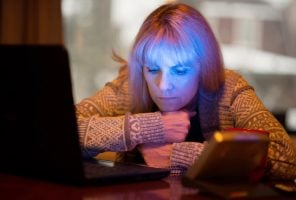 Middle-age woman with Seasonal affective disorder (SAD) working at home on computer with SAD LED light (lower right) which offers relief from seasonal depression.