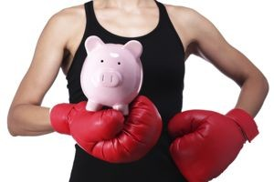woman in boxing gloves holding a saving pig