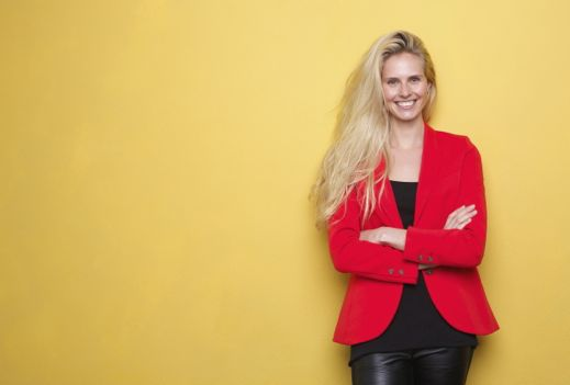 Woman in red jacket against yellow wall