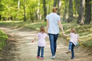 Woman with twin girls walking in the woods