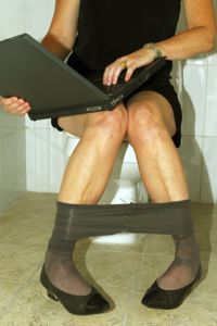 Woman on a toilet on her laptop