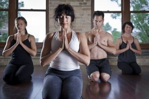 3 women and a man in a hot yoga class