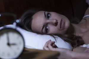 Woman with insomnia laying in bed staring at her clock
