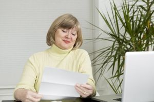 Older woman smiling as she opens her bank statement