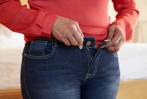 Close Up Of Overweight Woman Trying To Fasten Trousers In Bedroom Gaining Weight