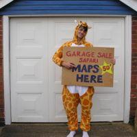 Man dressed as a giraffe holding a sign for garage safari sale