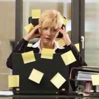 Multi-tasking business woman covered in post-it notes