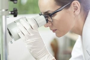 Woman doctor looking into a microscope