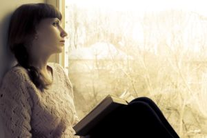 Woman looking out the window with a book in her lap