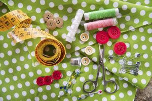 Sewing equipment laid out on a great and white fabric