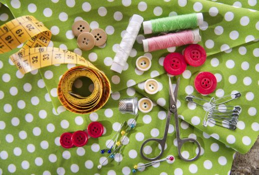 Sewing equipment laid out on a green and white fabric