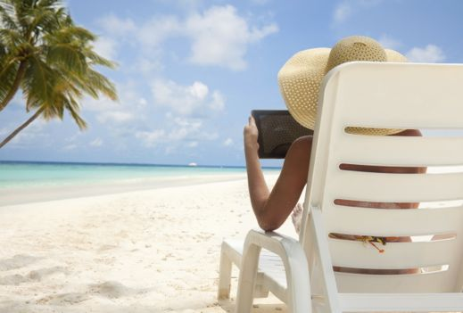 Woman on a white sandy beach reading from a tablet
