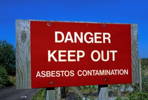 Red warning sign with the words 'Danger Keep Out Asbestos Contamination'