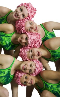 Synchronized swimmers wearing pink swimming hats and green costumes putting their heads together
