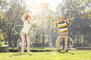 Mature couple exercising with hula hoops in park on a sunny day