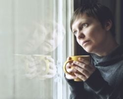 Lonely woman drinking cup of coffee by the window of her living room, looking out with a sad look on her face.