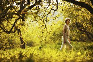 Woman walking in summer apple orchard