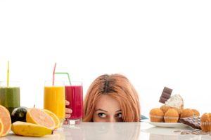 Woman choosing between fruits, smoothie and organic healthy food against sweets, sugar, lots of candies, unhealthy food.