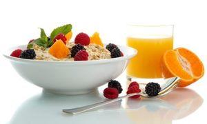 tasty porridge with berries and glass of juice