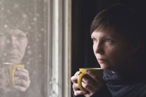 Lonelsome woman drinking cup of coffee by the window of her living room, looking out at snow falling with a sad look on her face.