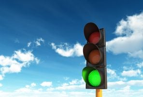 Traffic light on green against a sky background