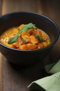Vegetable and red lentil soup in a black bowl on a wooden table