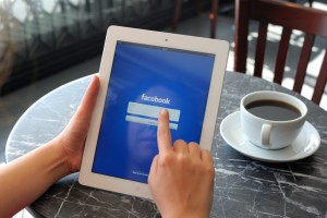 Woman looking at Facebook on an iPad at a cafe, with a cup of black coffee