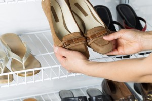 Woman taking out a pair of brown shoes from the wall mount rack to wear